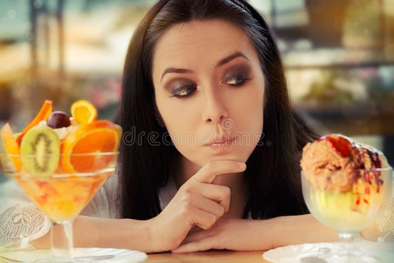 Ung kvinna som väljer mellan fruktsallad och glassefterrätter arkivbild