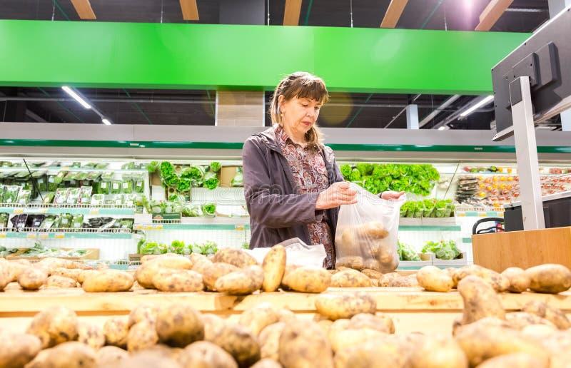 Ung kvinna som väljer nya potatisar på shopping i supermarket royaltyfri fotografi