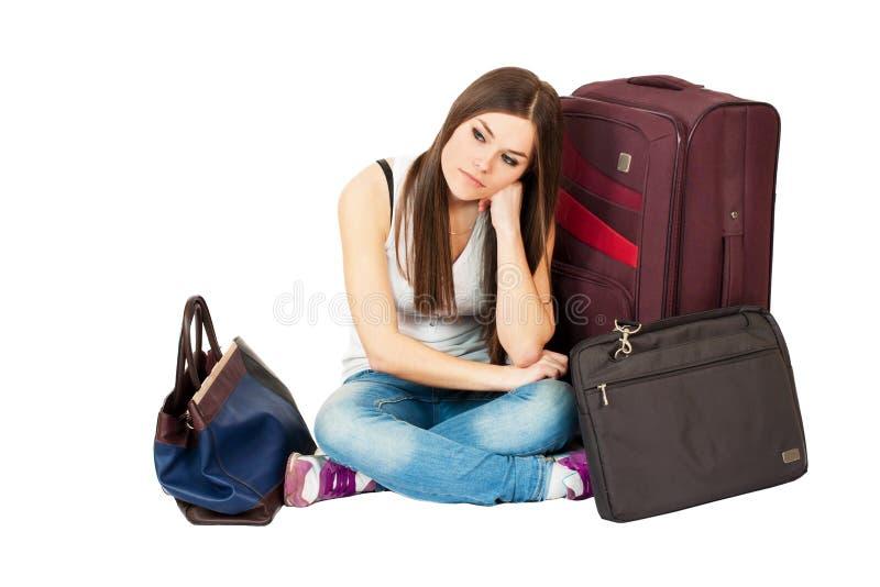 Ung kvinna som väntar på hennes flyg som evakueras med hennes bagage royaltyfria foton