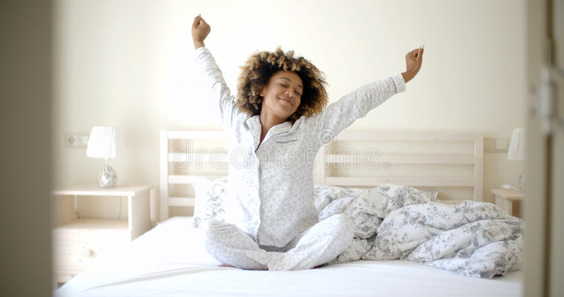Ung kvinna som vaknar på sängen fotografering för bildbyråer
