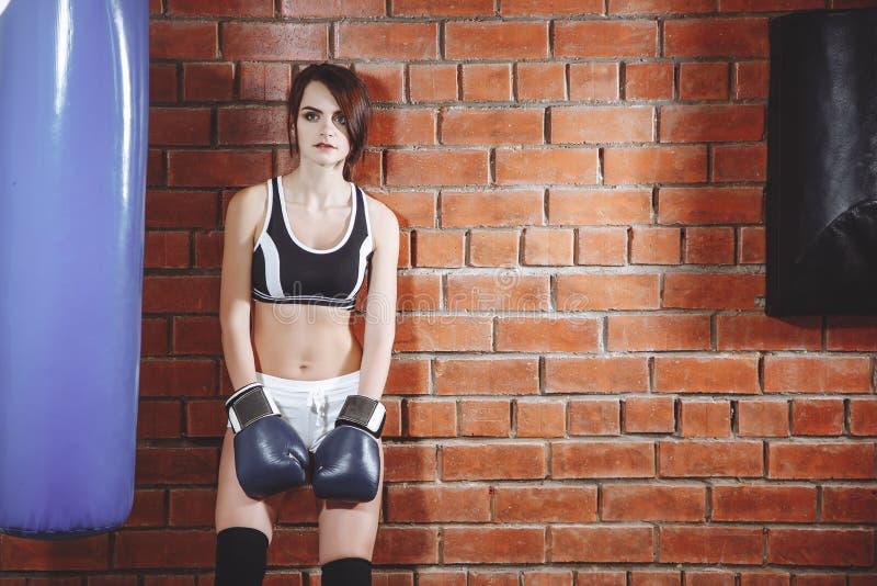 Ung kvinna som vilar efter en genomkörare i idrottshallen arkivbilder