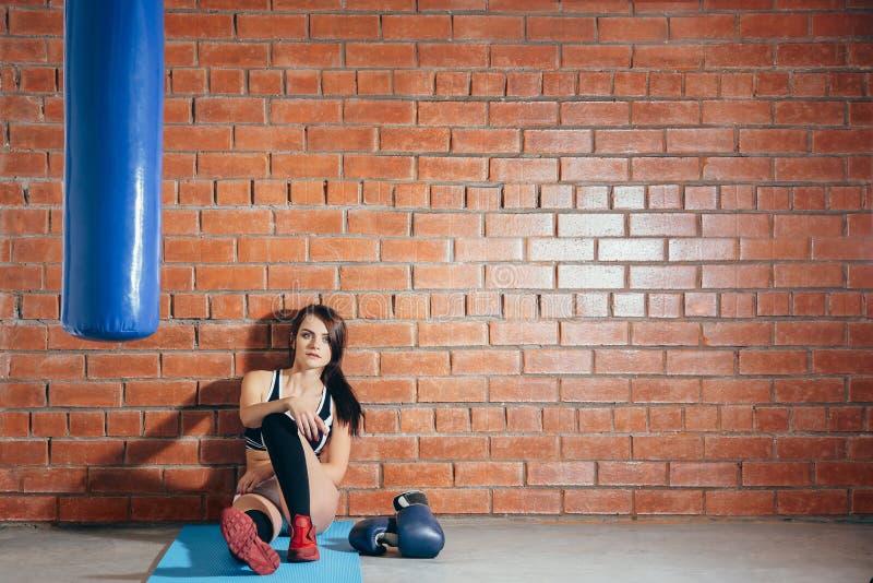 Ung kvinna som vilar efter en genomkörare i idrottshallen En flicka sitter på en bakgrund av en tegelstenvägg i korridoren av box fotografering för bildbyråer