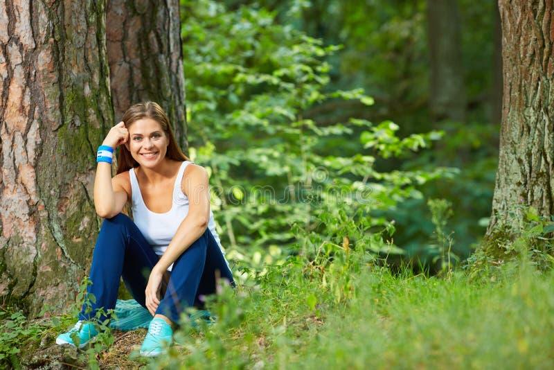 Ung kvinna som vilar i lös wood bakgrund för skoggräsplan royaltyfri bild