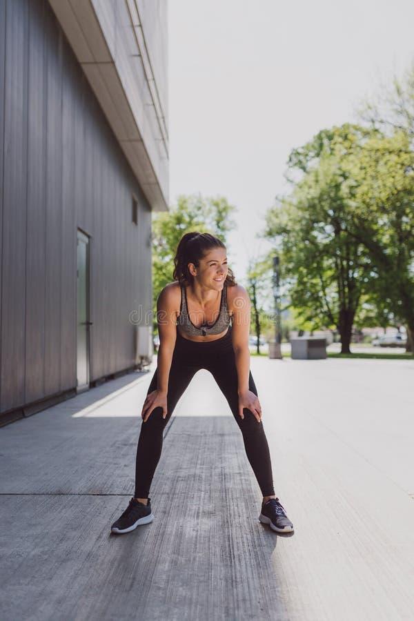 Ung kvinna som vilar, når att ha joggat arkivbilder