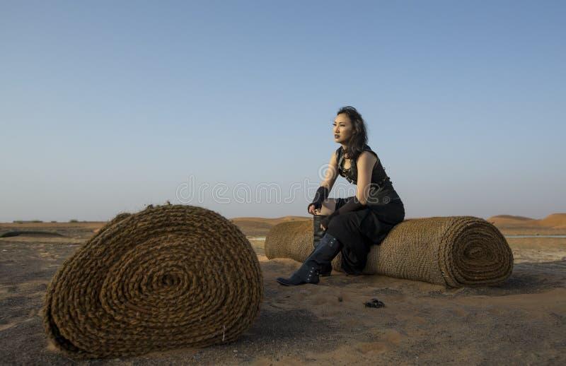 Ung kvinna som vilar på en gammal matta i en öken arkivbild