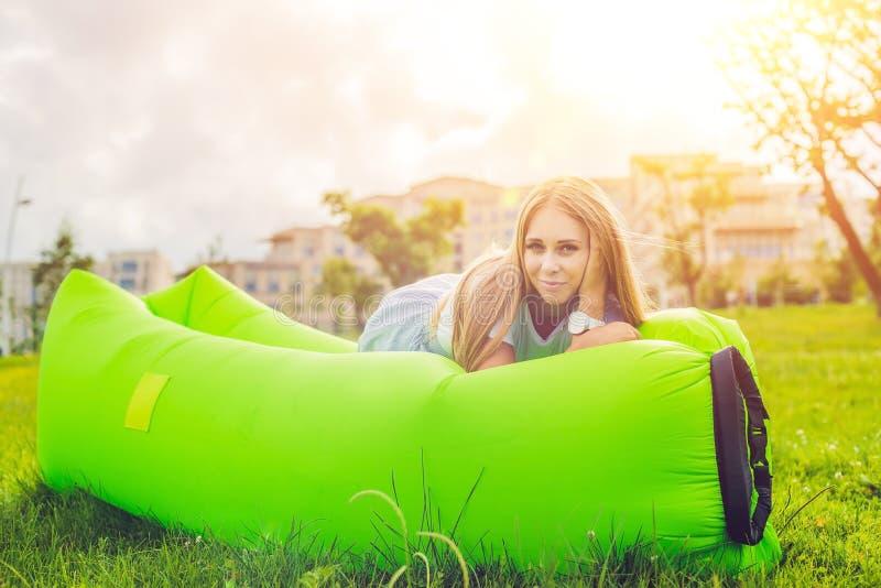 Ung kvinna som vilar på en luftsoffa i parkera royaltyfri foto