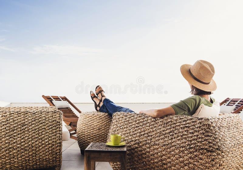 Ung kvinna som vilar på hotellterrass Semestrar och roligt begrepp för sommar Härlig flicka som tycker om livstid arkivfoto