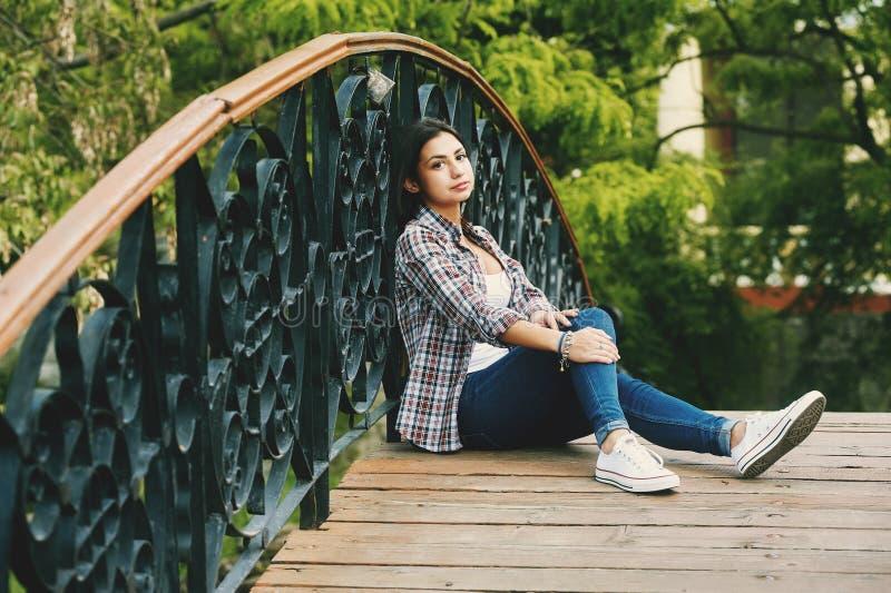 Ung kvinna som vilar sammanträde på en träbro royaltyfri foto