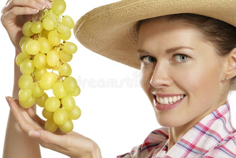 Ung kvinna som visar en grupp av druvor royaltyfri fotografi