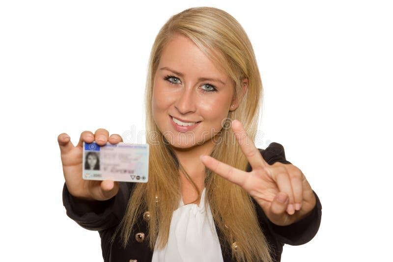 Ung kvinna som visar hennes körkort royaltyfri fotografi