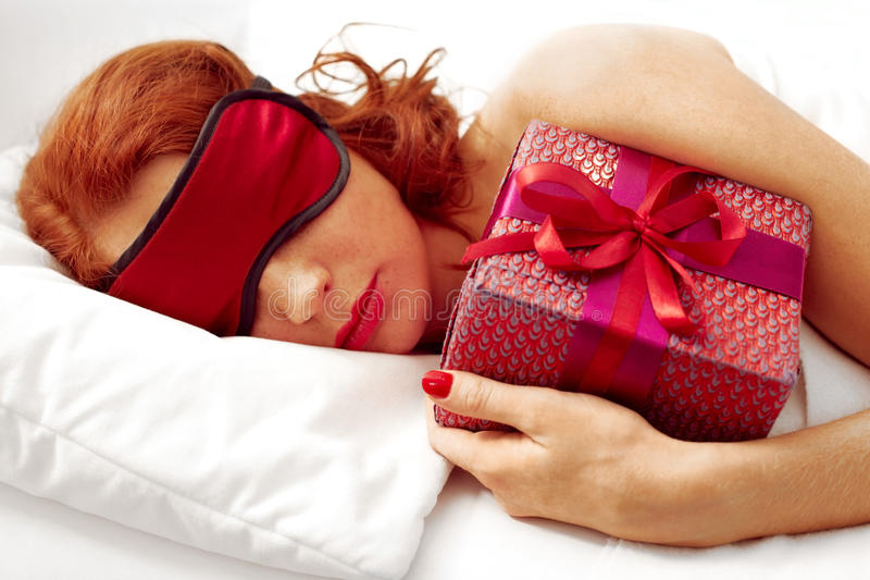 Ung kvinna sovande med gåvan arkivbild