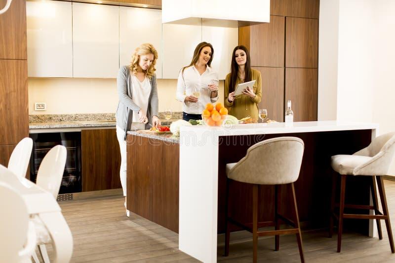 Ung kvinna tre i köket royaltyfri bild