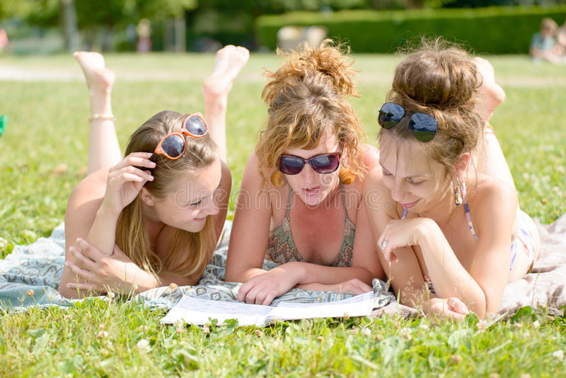 Ung kvinna tre på stranden som läser en tidskrift royaltyfria bilder