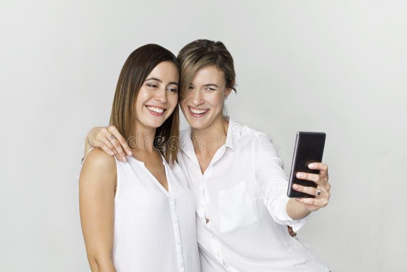 Ung kvinna två i den vita skjortan som har gyckel med danandeselfie ST arkivbild