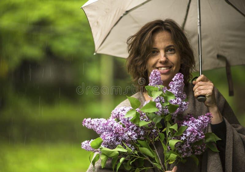Ung kvinna under ett paraply med en bukett av lilan i hand under regn royaltyfri fotografi