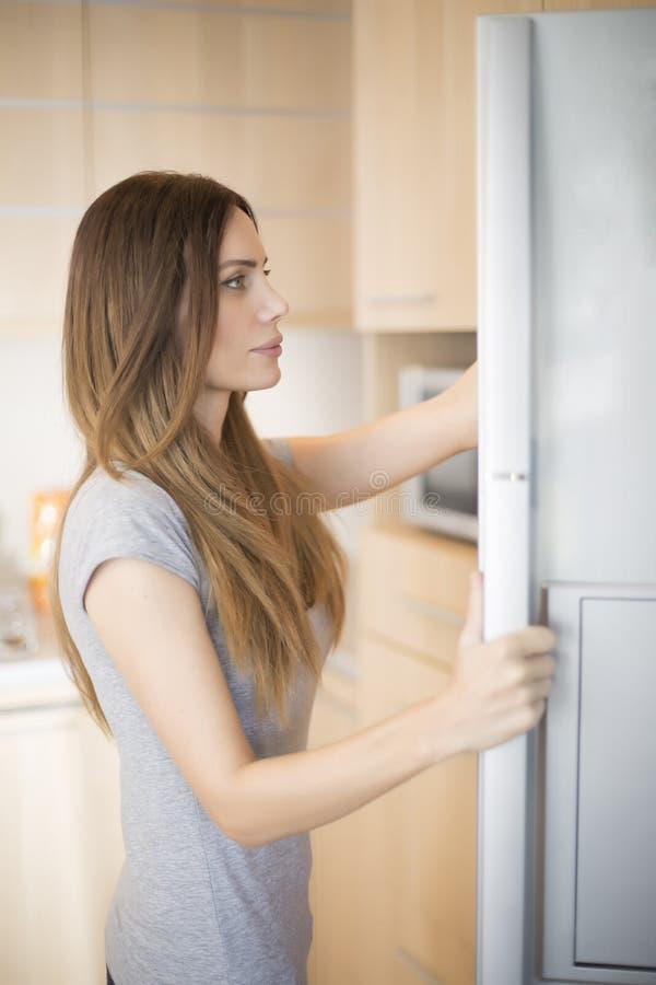 Ung kvinna vid kylskåpet royaltyfria foton