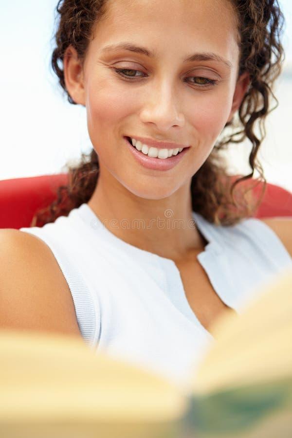 Ung kvinnaavläsningsbok royaltyfria foton