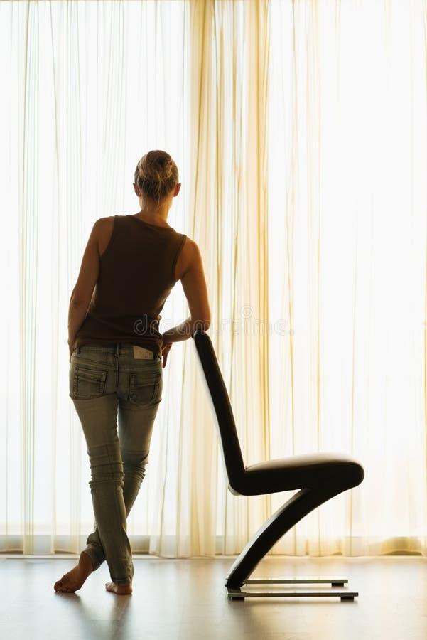 Ung kvinnabenägenhet mot modern stol. Baksidan tävlar arkivfoton