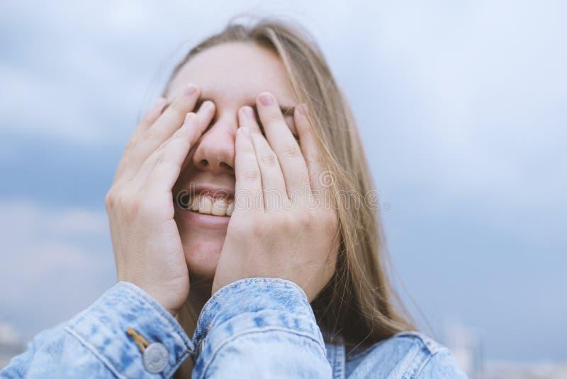 Ung kvinnacovering henne ?gon med henne h?nder Positiva sinnesrörelser, skratt, leende, glädje arkivbild
