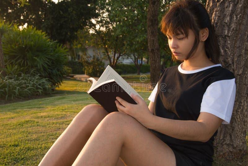 Ung kvinnaläsning bokar Closeup av en härlig rea för ung kvinna royaltyfri foto
