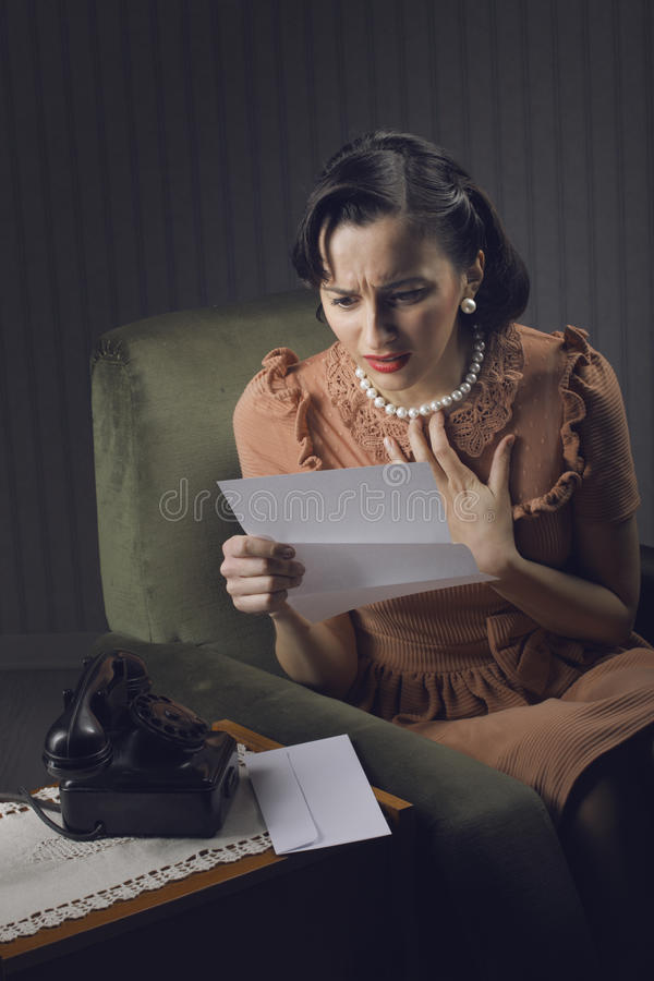 Kvinnaläsning en märka med bekymrat uttryck royaltyfri foto