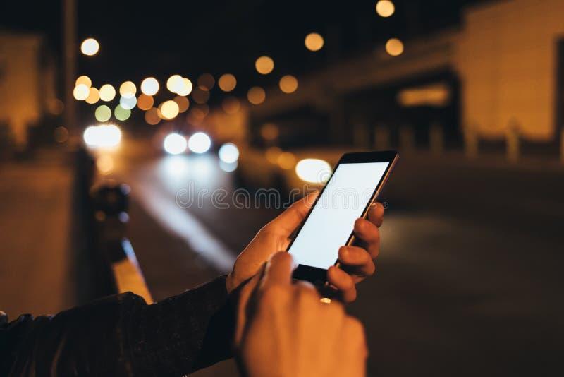 Ung kvinnas för närbild som händer rymmer mobilen arkivbilder