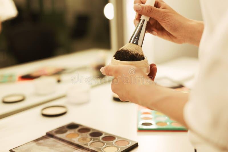 Ung kvinnas händer som rymmer makeupborsten och pulver mot spegeln royaltyfri fotografi