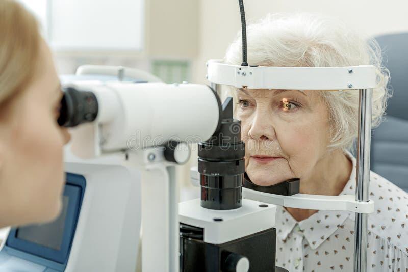 Ung kvinnlig ögonläkare som använder apparaturen royaltyfri foto