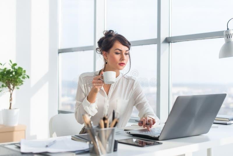 Ung kvinnlig affärsperson som i regeringsställning arbetar genom att använda bärbara datorn, läsning och söka information uppmärk arkivbild