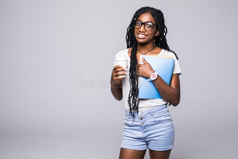 Ung kvinnlig afrikansk amerikanhögskolestudent i exponeringsglas som rymmer böcker isolerade på vit arkivbilder