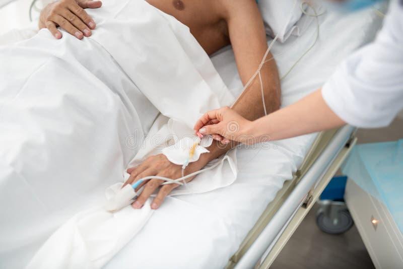 Ung kvinnlig anesthesiologist som tar omsorg av patienten efter kirurgi arkivbild