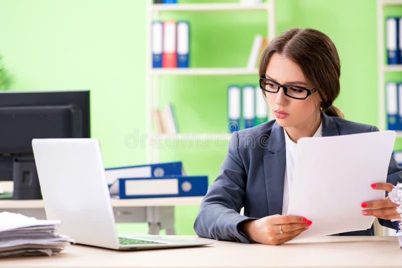 Ung kvinnlig anställd som mycket är upptagen med pågående skrivbordsarbete royaltyfri bild