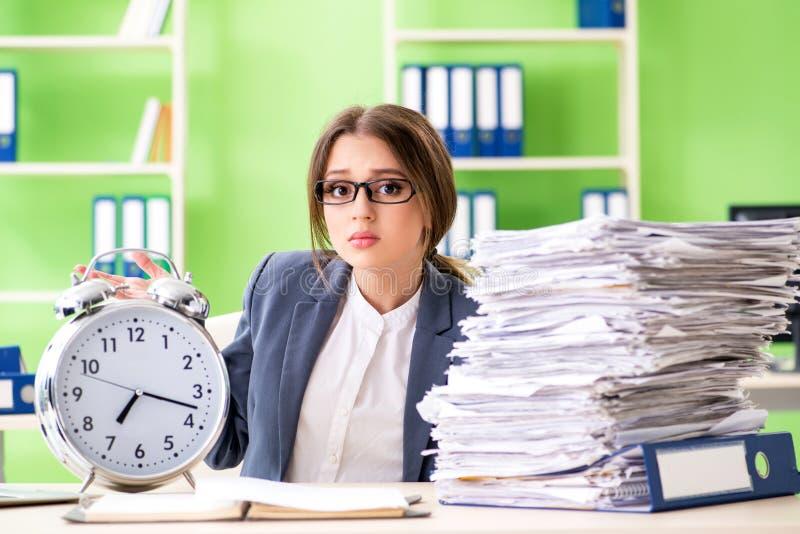 Ung kvinnlig anställd som mycket är upptagen med pågående skrivbordsarbete i tid M royaltyfri fotografi
