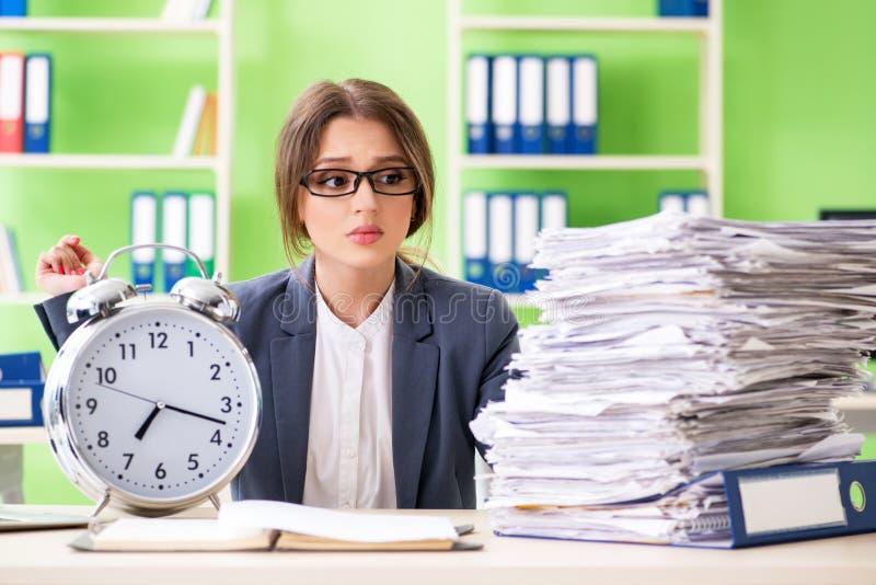 Ung kvinnlig anställd som mycket är upptagen med pågående skrivbordsarbete i tid M arkivbild