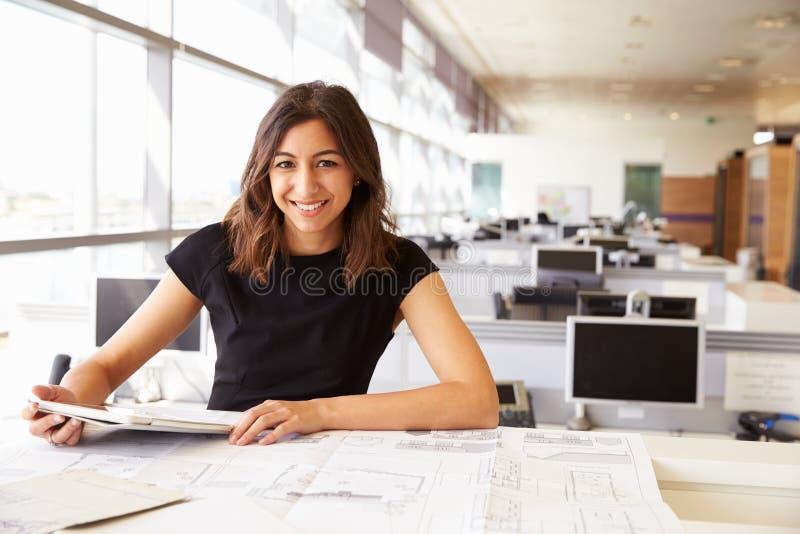 Ung kvinnlig arkitekt som arbetar med datoren och ritningar royaltyfri foto