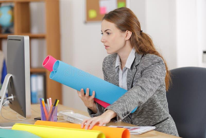 Ung kvinnlig arkitekt som i regeringsställning arbetar på blått tryck arkivfoton
