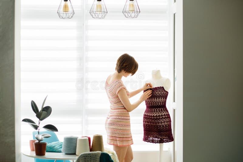 Ung kvinnlig bekläda formgivare som använder klänningattrappen på den hemtrevliga hemmiljön, frilans- livsstil royaltyfri foto