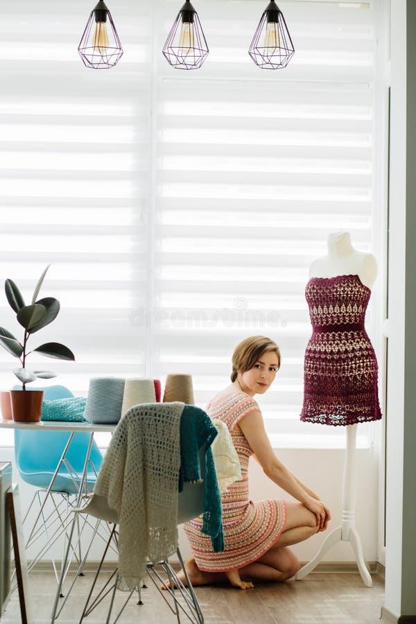 Ung kvinnlig bekläda formgivare som använder klänningattrappen på den hemtrevliga hemmiljön, frilans- livsstil Skjuten lodlinje royaltyfria bilder