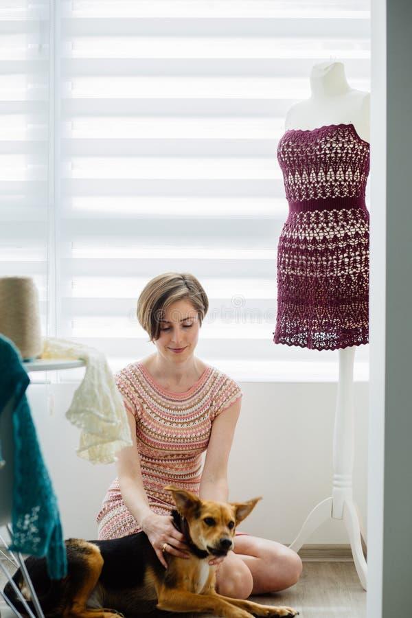 Ung kvinnlig bekläda formgivare som kopplar av med hennes hund Nära klänningattrapp på den hemtrevliga hemmiljön, frilans- livsst arkivfoton