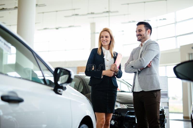 Ung kvinnlig bilförsäljningskonsulent som arbetar i visningslokal royaltyfria foton