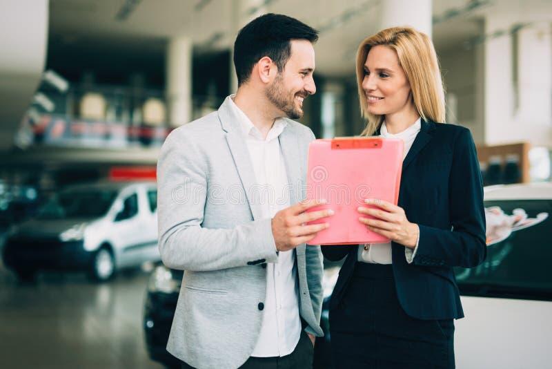 Ung kvinnlig bilförsäljningskonsulent som arbetar i visningslokal royaltyfri fotografi