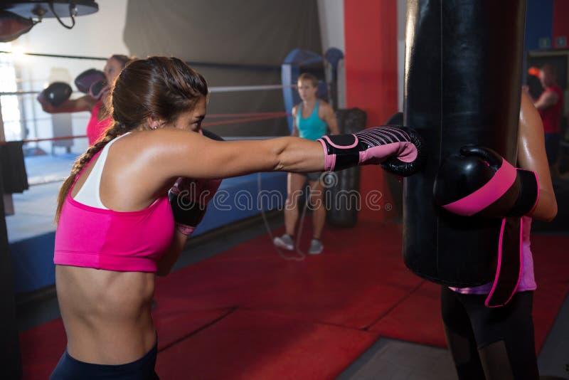 Ung kvinnlig boxare som stansar den svarta påsen arkivbild