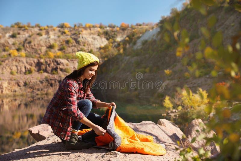 Ung kvinnlig campare som packar upp sovsäcken i vildmark royaltyfri bild