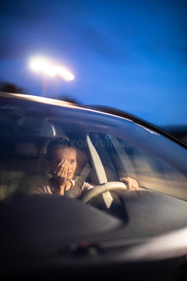 Ung kvinnlig chaufför på hjulet av hennes bil, toppet trött arkivfoto