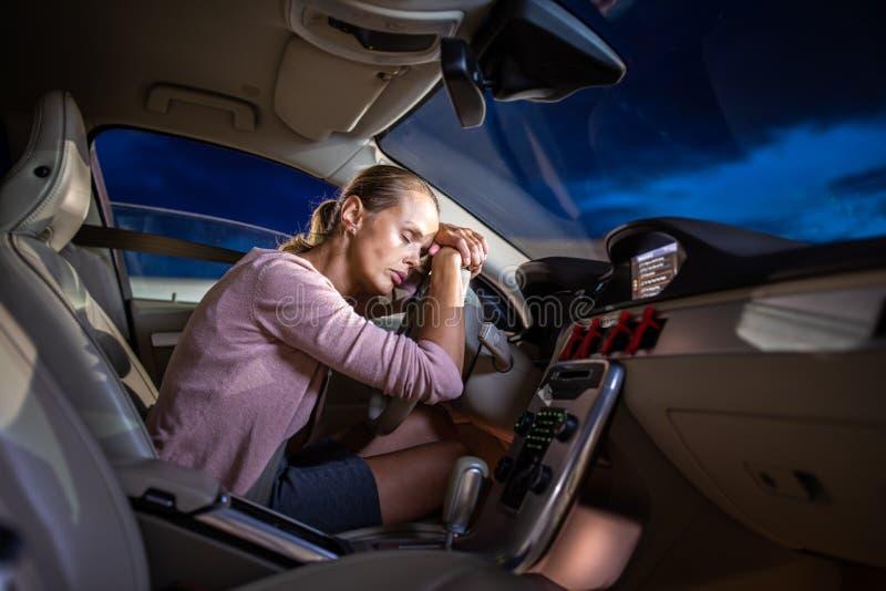 Ung kvinnlig chaufför på hjulet av hennes bil, toppet trött fotografering för bildbyråer