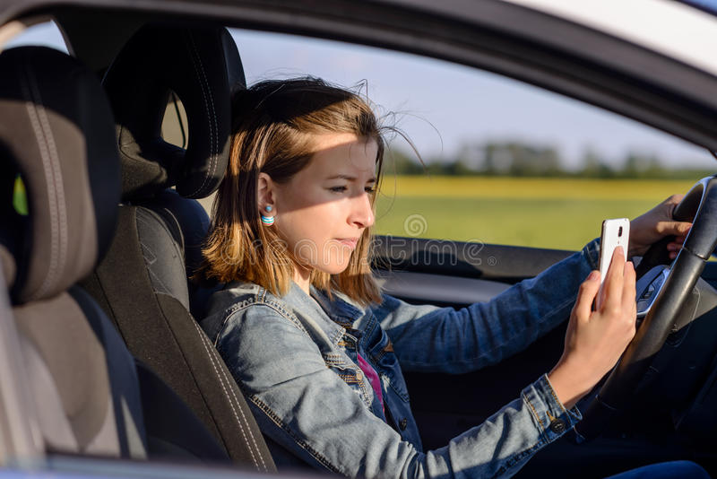 Ung kvinnlig chaufför som läser ett textmeddelande royaltyfri bild