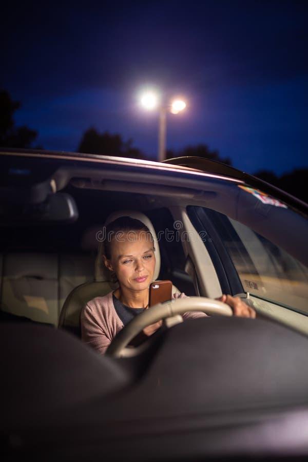 Ung kvinnlig chauff?r som spelar med hennes mobiltelefon fotografering för bildbyråer