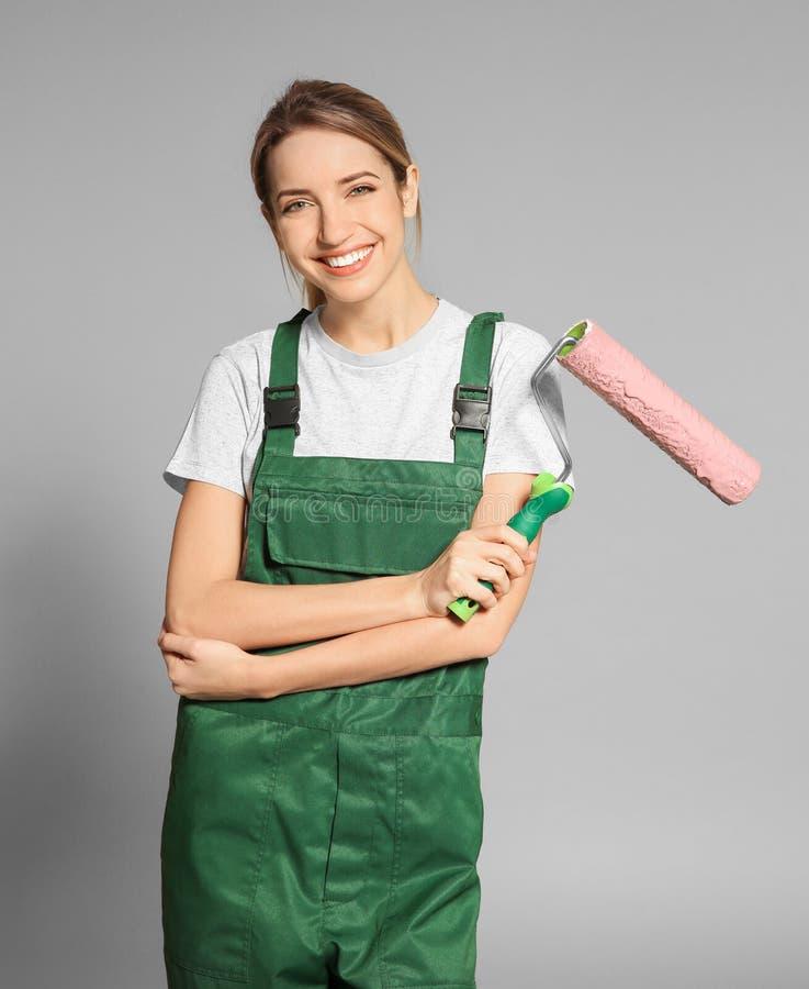 Ung kvinnlig dekoratör med målarfärgrullen fotografering för bildbyråer