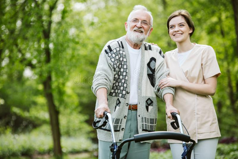 Ung kvinnlig deltagare i utbildning med äldre man i vårdhemmet royaltyfri foto