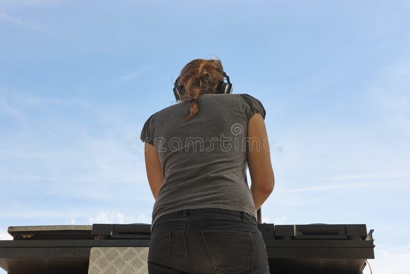 Ung kvinnlig dj med bakgrund för blå himmel utomhus- deltagare arkivfoto